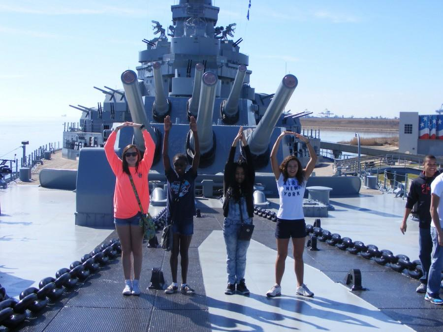 Junior Taylor Mason stands with sophomores Melissa Barrett, Kiana Hayes, and Taylor Evans in front of the 16-inch gun turrets of the battleship USS Alabama (photograph by John Garrison, Yearbook Staff)