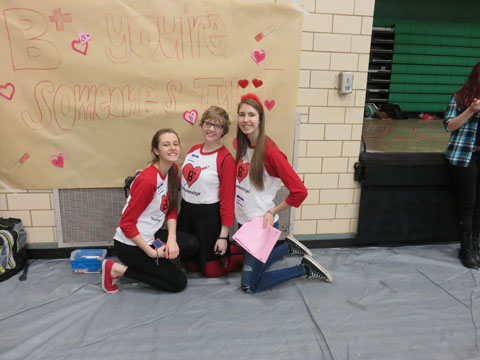 Seniors Eva Stebel and Tori Amos and freshman Cecelia Stebel take a break to work on the poster