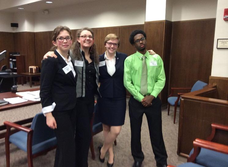 Junior Gracie Fink stands with seniors Erin Brown, Tori Amos, and Richie Bullard at their Mock Trial competition.