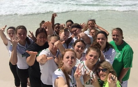 The varsity softball team stands on the beach with junior pitcher Mallory Woods' selfie stick.