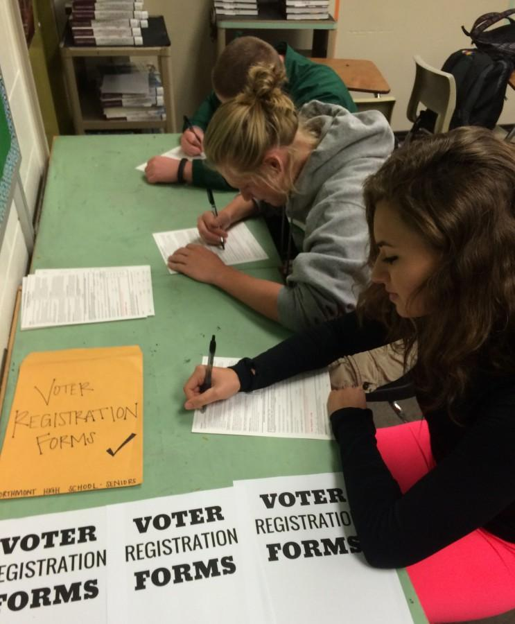 Junior Dillon Black and seniors Garrett Boeckman, and Courtney Eilerman register for voting. Issue 3 will be on the ballot.