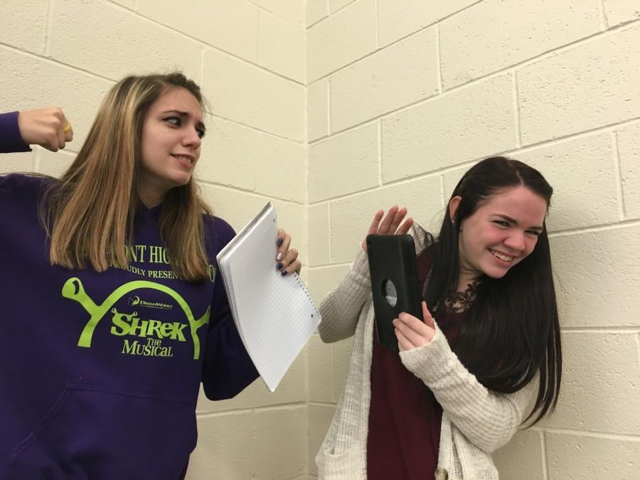 Senior Shelby Didier and sophomore Sammie Helmund depict the iPad versus paper debate.