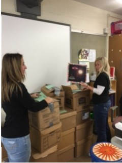 Junior Anya Young helps Spanish teacher Ms. Jenna Harris pack for the move to the new building.