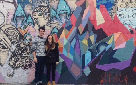 Juniors Nicholle Weidner and Cole Peyton stand in front of a piece of graffiti art in Columbus, Ohio.