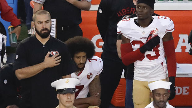 Colin Kaepernick kneels as the national anthem plays (Courtesy of CBSNews.com)