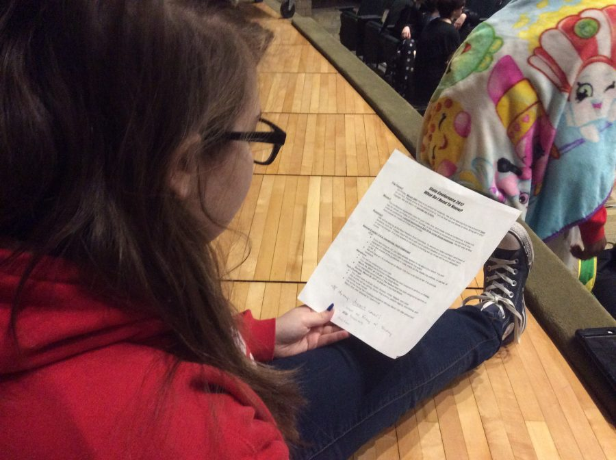 Freshman Lindsi Tomlinson looks over the state conference information sheet.