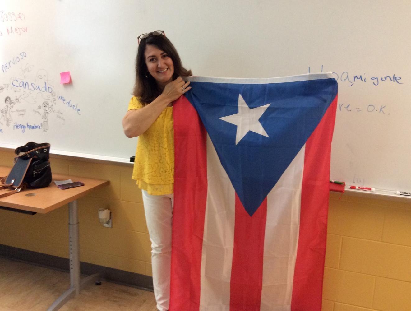 Ms. Sandra Ocasio holds the Puerto Rican flag.