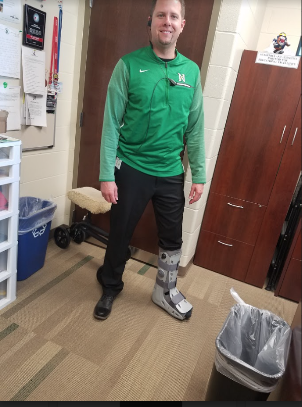 Mr. Micah Harding wears a boot to protect his torn Achilles tendon