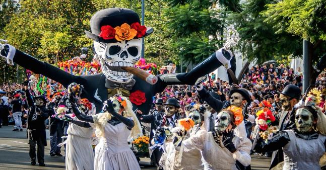A parade celebrating El Día de los Muertos makes its way down a street in Mexico (courtesy of Claudia Dozias).