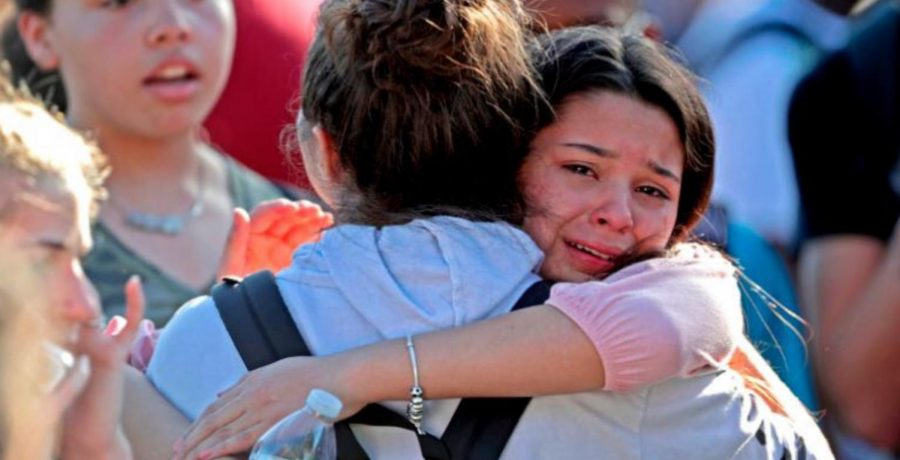 A person mourns victims of the Parkland shooting (courtesy of CNN).