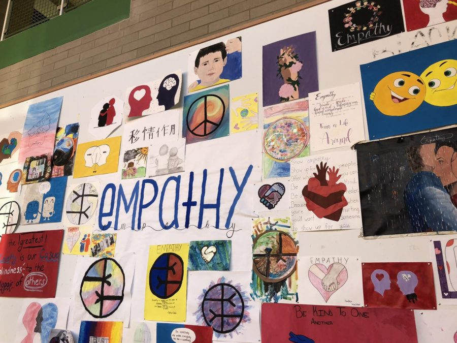 The empathy wall is a bulletin board in the main hallway with students' artwork on display.