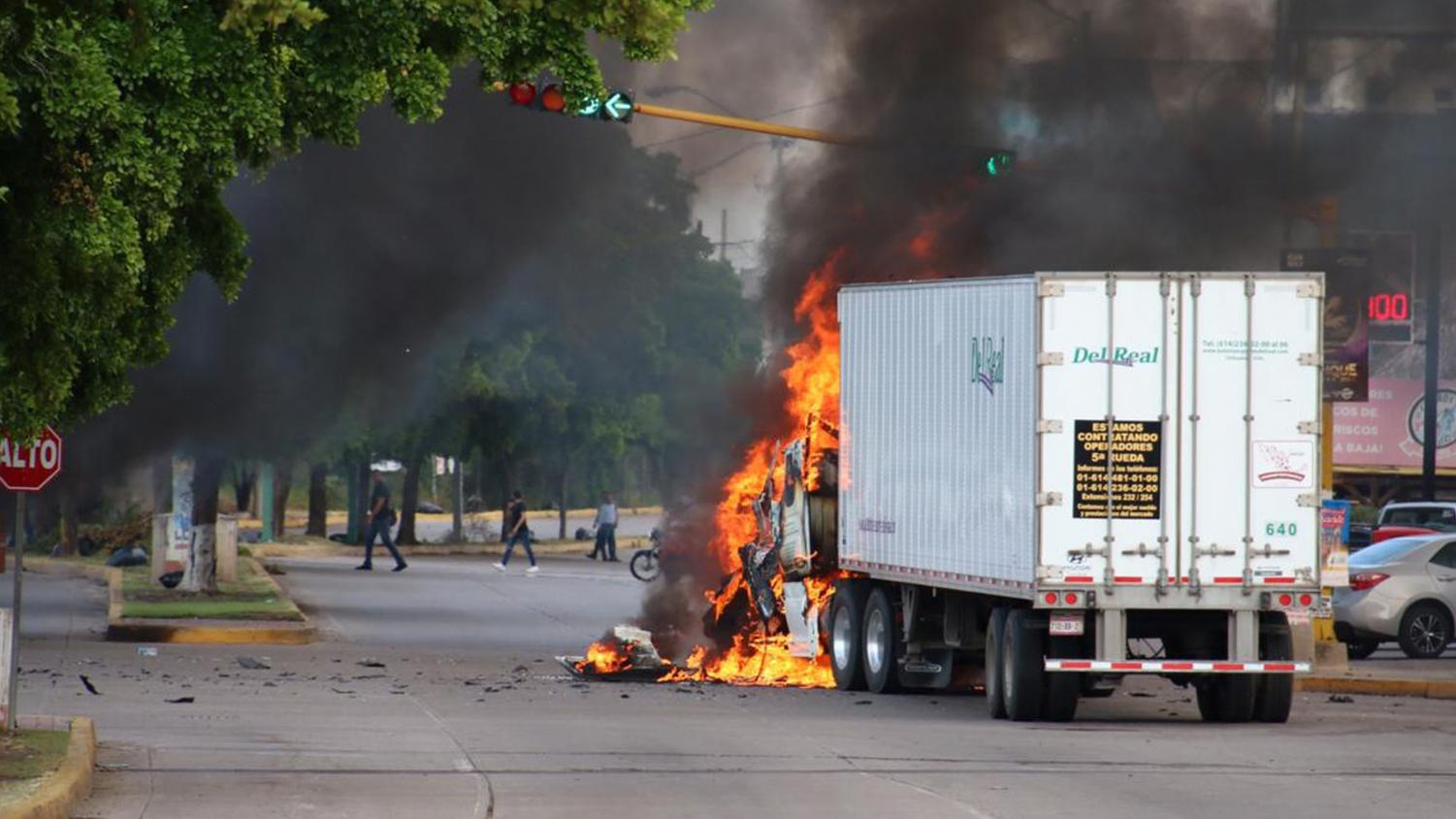Cars burn in the street as fighting rages.