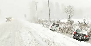 A car pulled over to the side of the road during the snow storm.