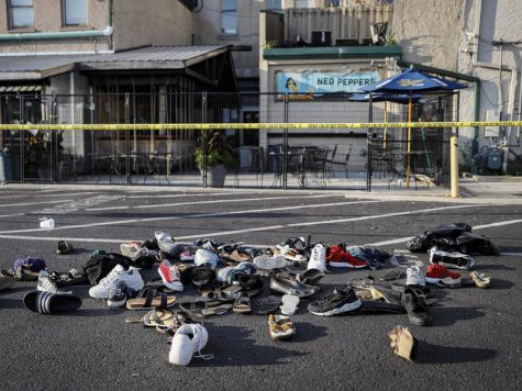 Shoes of the victims are piled at the scene of the shooting. John Minchillo/AP