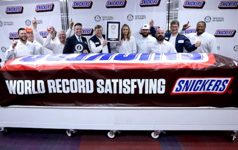 Mars Wrigley employees pose Thursday, Jan. 16, 2020, with a giant Snickers bar made at the Hewitt plant in Waco, Texas.  Guinness world records recognized the Snickers as the largest chocolate nut bar.  (Jerry Larson/Waco Tribune-Herald via AP)