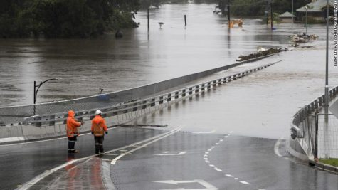 Traffic controllers stand at the Hawkesbury River Bridge submerged by floodwaters in Windsor, New South Wales, Australia, on Monday, March 22, 2021. Western Sydney and the NSW Mid-North coast are bearing the brunt of the relentless downpour that has caused the Warragamba Dam, Sydney???s primary source of water, to overflow for the first time in five years, and caused severe damage to property and roads. Photographer: Brent Lewin/Bloomberg