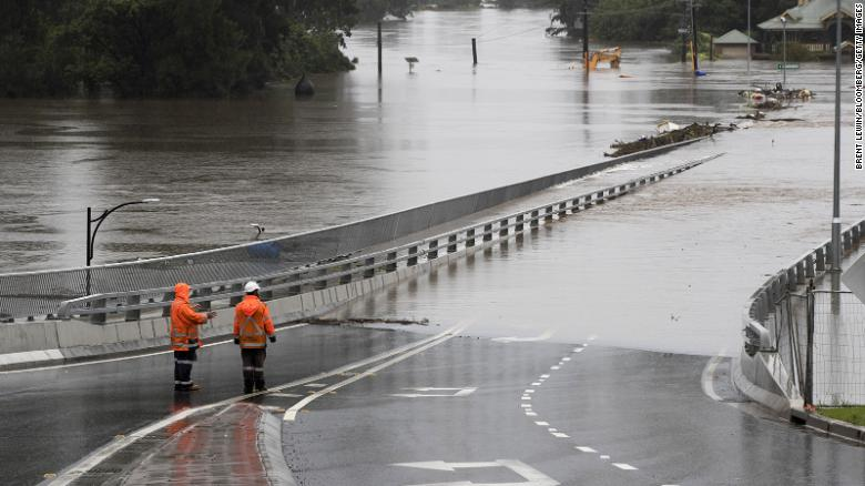 Traffic+controllers+stand+at+the+Hawkesbury+River+Bridge+submerged+by+floodwaters+in+Windsor%2C+New+South+Wales%2C+Australia%2C+on+Monday%2C+March+22%2C+2021.+Western+Sydney+and+the+NSW+Mid-North+coast+are+bearing+the+brunt+of+the+relentless+downpour+that+has+caused+the+Warragamba+Dam%2C+Sydney%3F%3F%3Fs+primary+source+of+water%2C+to+overflow+for+the+first+time+in+five+years%2C+and+caused+severe+damage+to+property+and+roads.+Photographer%3A+Brent+Lewin%2FBloomberg