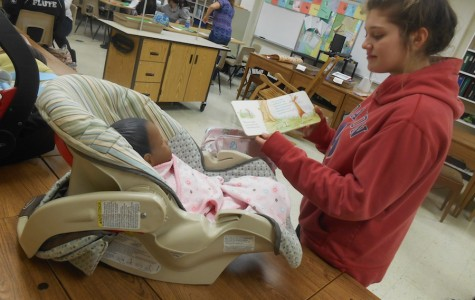 Sophomore Ally Ratzel reads a children's book to the baby she has been assigned in Parenting class. Northmont's Parenting class focuses on parenting skills and child development, which bring awareness to the struggles of raising an infant.