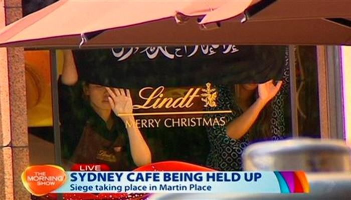 Hostages+are+forced+to+hold+up+an+Islamic+flag+in+the+window+of+the+Lindt+Cafe+in+Sydney%2C+Australia+%28photo+courtesy+of+ksbw.com%29.