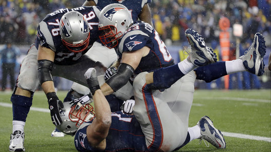 New England Patriots tackle Nate Solder is congratulated by his teammates after scoring on a 16-yard touchdown pass during the second half of the NFL football AFC Championship game against the Indianapolis Colts Sunday, Jan. 18, 2015, in Foxborough, Mass. (AP Photo/Matt Slocum - Photo courtesy of Huffington Post)