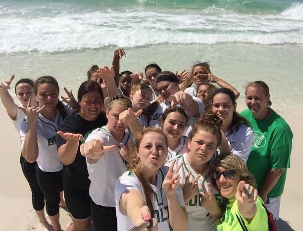 The+varsity+softball+team+stands+on+the+beach+with+junior+pitcher+Mallory+Woods%27+selfie+stick.