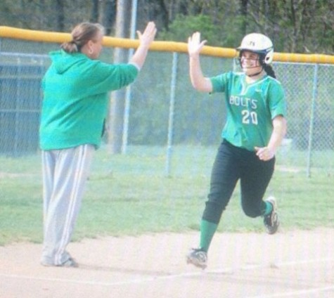Junior Lizzie Ritchie gives coach Mangen a high five as she rounds third base. Photo courtesy of: Northmont Yearbook