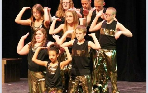 Senior Dustin Kallmeyer stands at the back of his hip hop dance crew at their May recital in the high school auditorium.