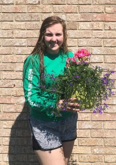 Sophomore Maddie Jaehnen holds flowers at Englewood Florist, her place of work for the summer.