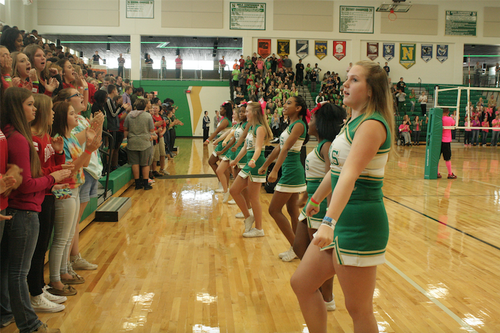 Cheerleaders lead the crowd of freshmen at the first pep rally in the new school.
