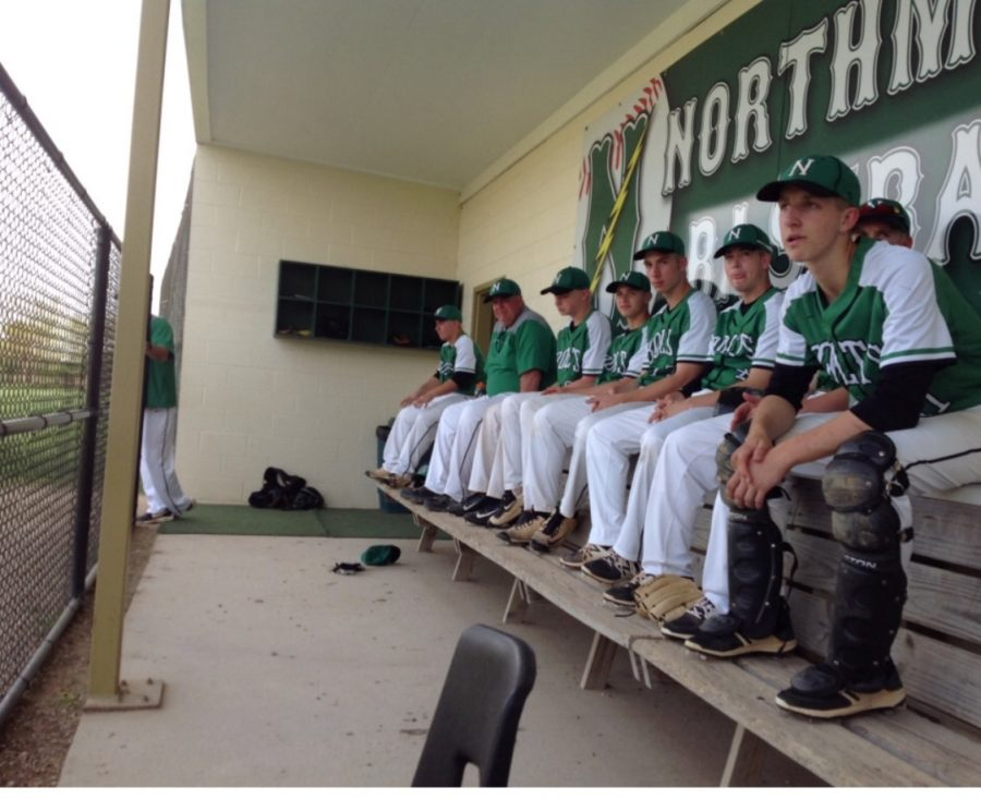 The varsity baseball teams sits in the dugout before a game (courtesy of Northmont Athletics).