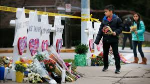 Men, women, and children pay their respects to the victims of the shooting.