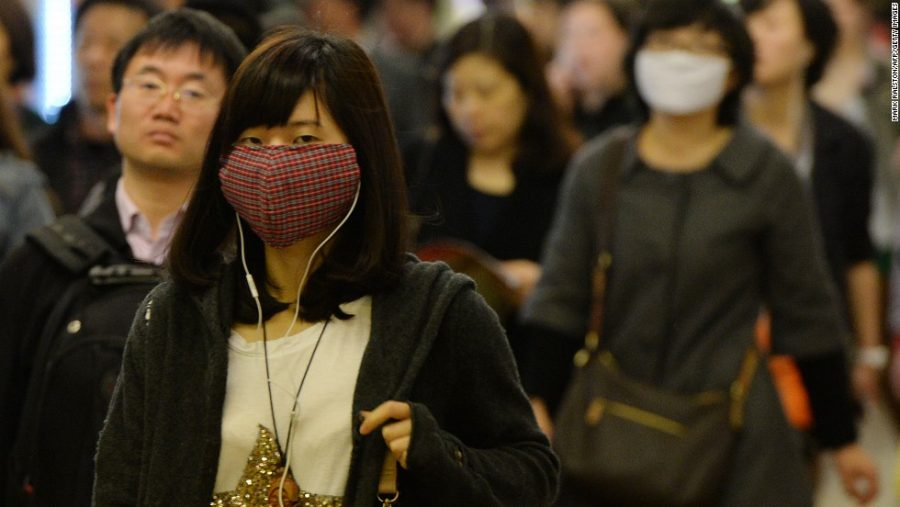 Women wear facemasks as the city's commuters protect themselves against the H7N9 bird flu virus in the downtown area of Shanghai in 2013 (Photo courtesy of CNN).